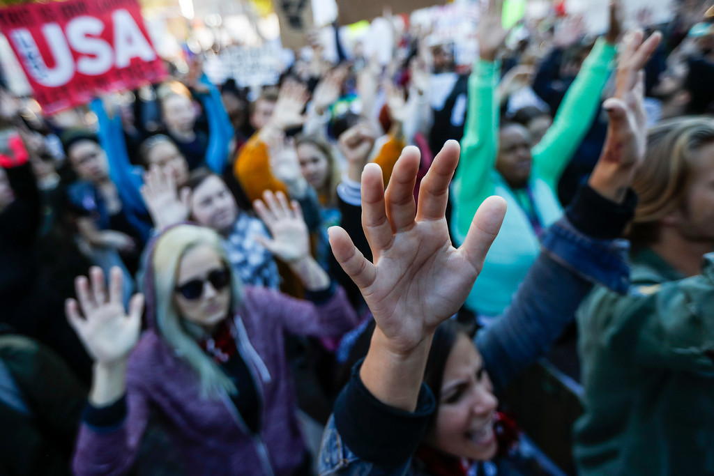 . Protestors raise their hands in defiance at a rally in Washington Park after a mistrial was declared due to a hung jury in the murder trial against Ray Tensing, Saturday, Nov. 12, 2016, in Cincinnati. Tensing, a white former University of Cincinnati police officer, was charged with murder in the shooting of Sam DuBose, an unarmed black motorist, while on duty during a routine traffic stop on July 19, 2015. (AP Photo/John Minchillo)