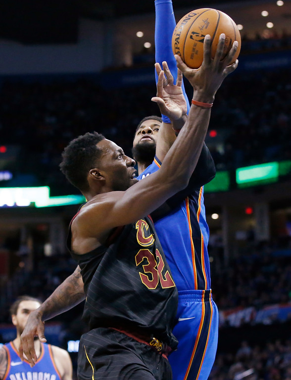 . Cleveland Cavaliers forward Jeff Green (32) is fouled by Oklahoma City Thunder forward Paul George during the first half of an NBA basketball game in Oklahoma City, Tuesday, Feb. 13, 2018. (AP Photo/Sue Ogrocki)