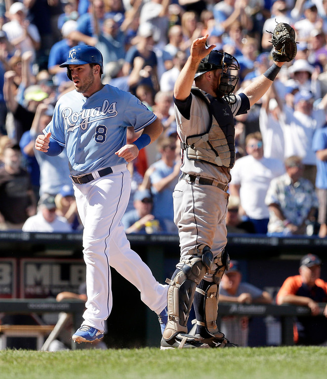 . Kansas City Royals\' Mike Moustakas (8) runs past Detroit Tigers catcher Bryan Holaday to score on a two-run triple by Norichika Aoki during the fourth inning of a baseball game Sunday, Sept. 21, 2014, in Kansas City, Mo. (AP Photo/Charlie Riedel)