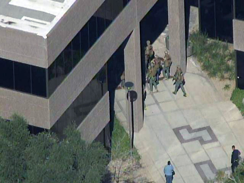 . This frame grab provided by abc15.com shows the scene at a Phoenix office complex where police say a gunman shot at least three people on Wednesday, Jan. 30, 2013. Officer James Holmes said the victims were taken to hospitals and did not know if their injuries were life threatening. (AP Photo/abc15.com)