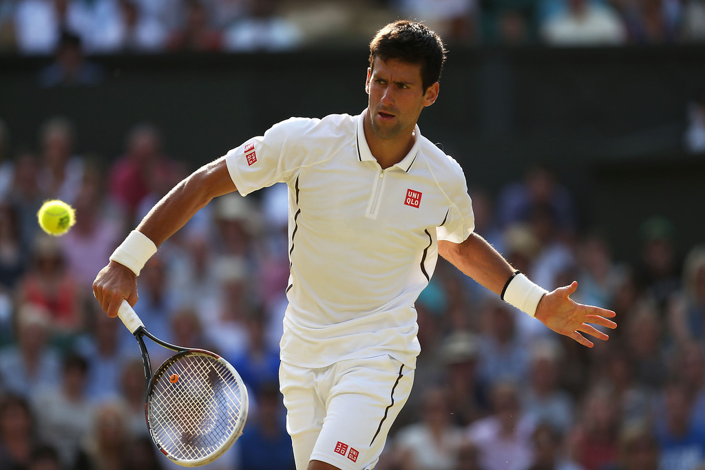 . LONDON, ENGLAND - JULY 05:  Novak Djokovic of Serbia plays a backhand during the Gentlemen\'s Singles semi-final match against Juan Martin Del Potro of Argentina on day eleven of the Wimbledon Lawn Tennis Championships at the All England Lawn Tennis and Croquet Club on July 5, 2013 in London, England.  (Photo by Clive Brunskill/Getty Images)
