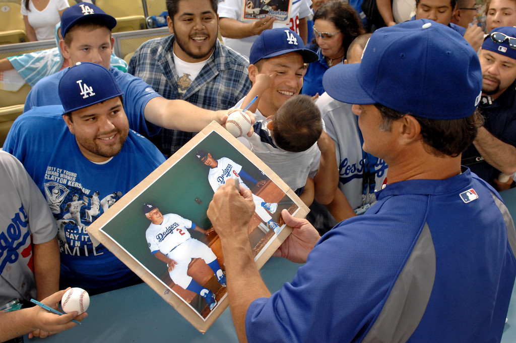 . Dodger manager Don Mattingly signs a picture of himself and Tommy Lasorda, Thursday, July 12, 2012, at Dodger Stadium. (Michael Owen Baker/Staff Photographer)
