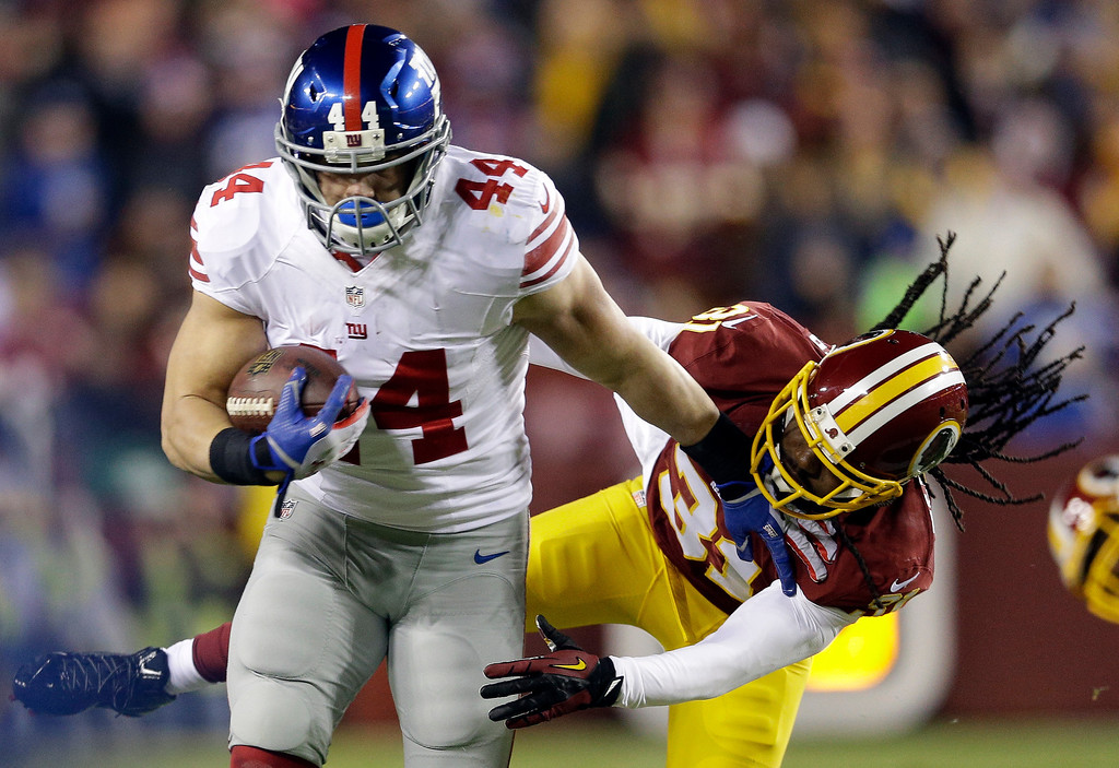 . New York Giants running back Peyton Hillis (44) pushes away Washington Redskins strong safety Brandon Meriweather (31), for a first down, during the first half of an NFL football game Sunday, Dec. 1, 2013, in Landover, Md. (AP Photo/Patrick Semansky)