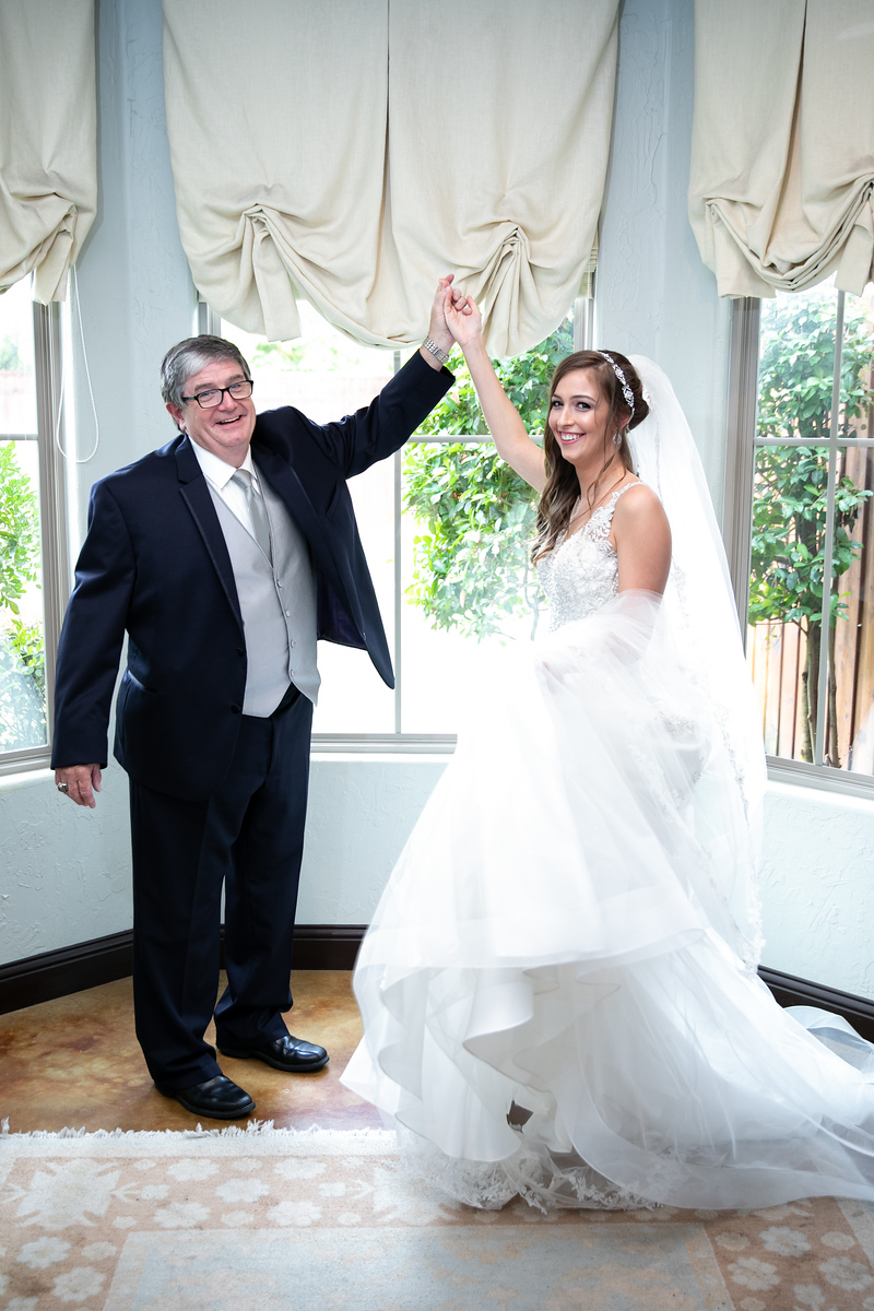 a father holding up the hand of his daughter on the day of her wedding before the ceremony