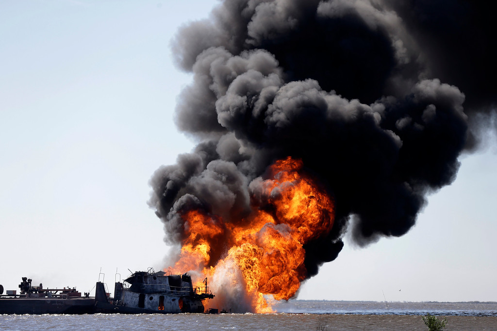 . A fire still burns after a tugboat and barge hit a gas pipeline yesterday evening in Perot Bay in Lafourche Parish, La., Wednesday, March 13, 2013. (AP Photo/Gerald Herbert)