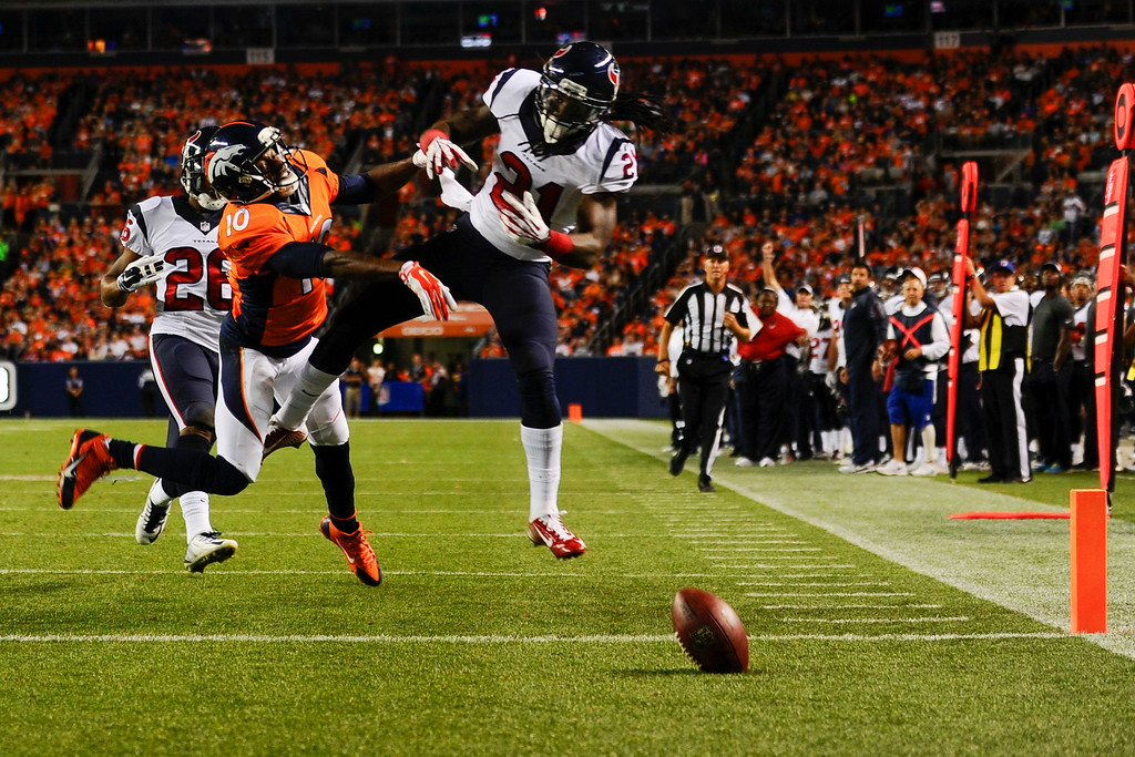 . DENVER, CO - AUGUST 23:  Kendrick Lewis (21) of the Houston Texans breaks up a pass intended for Emmanuel Sanders (10) from Peyton Manning (18) of the Denver Broncos during a preseason football game at Sports Authority Field at Mile High on Saturday, August 23, 2014 in Denver, Colorado.  (Photo by Kent Nishimura/The Denver Post)
