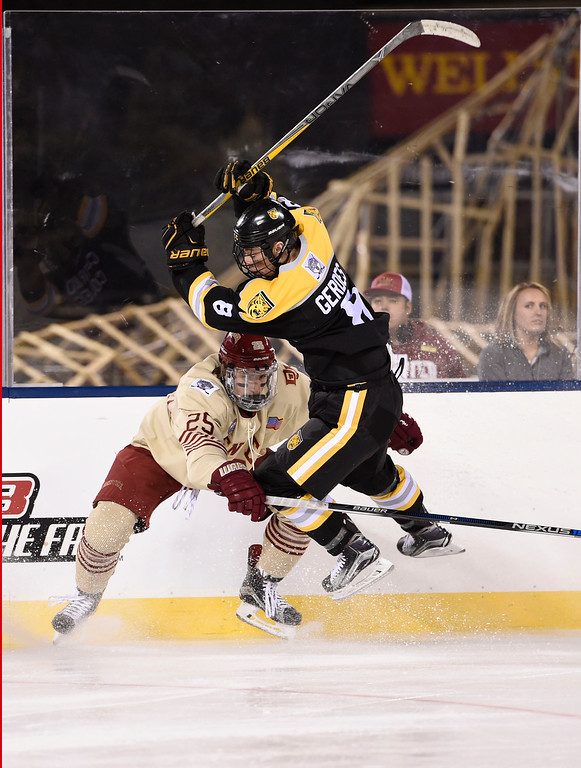 . Denver Pioneers defenseman Blake Hillman (25) slams in to Colorado College Tigers forward Luc Gerdes (8) in the first period during the Battle On Blake February 20, 2016 at Coors Field.  (Photo By John Leyba/The Denver Post)