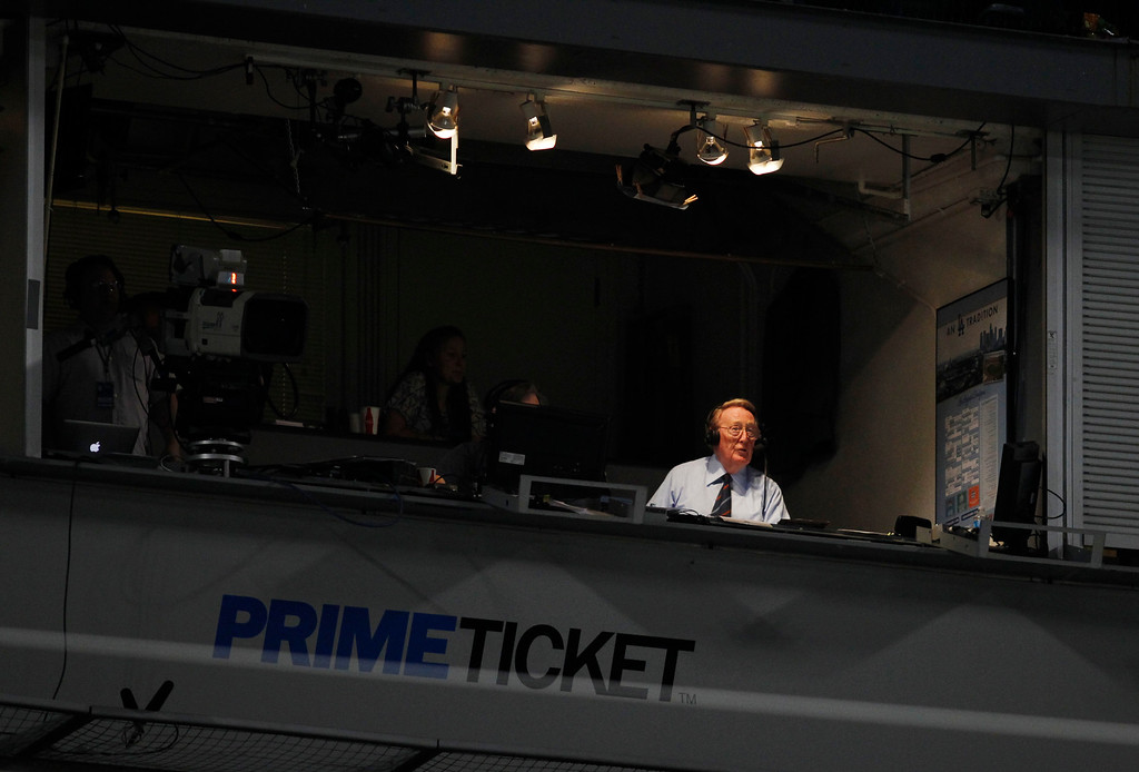 . Sportscaster Vin Scully broadcasts from a press box booth at Dodger Stadium during the MLB exhibition baseball game between the Los Angeles Angels and Los Angeles Dodgers Tuesday, April 3, 2012, in Los Angeles. (AP Photo/Danny Moloshok)