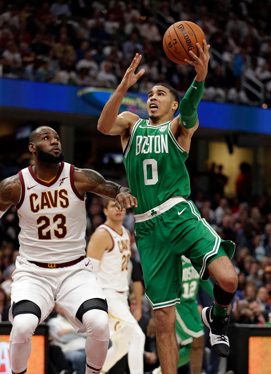 . Boston Celtics\' Jayson Tatum (0) drives against Cleveland Cavaliers\' LeBron James (23) in the first half of an NBA basketball game, Tuesday, Oct. 17, 2017, in Cleveland. The Cavaliers won 102-99. (AP Photo/Tony Dejak)