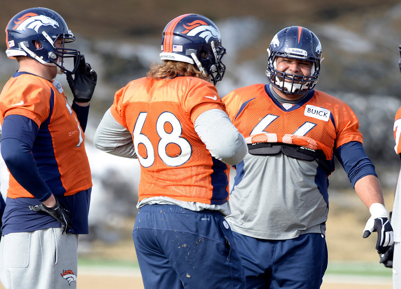 . Denver Broncos center Manny Ramirez (66) smiles after picking yup Denver Broncos guard Zane Beadles (68) off the ground during practice January 16, 2014 at Dove Valley. The Denver Broncos are preparing for their AFC Championship game against the New England Patriots at Sports Authority Field.  (Photo by John Leyba/The Denver Post)
