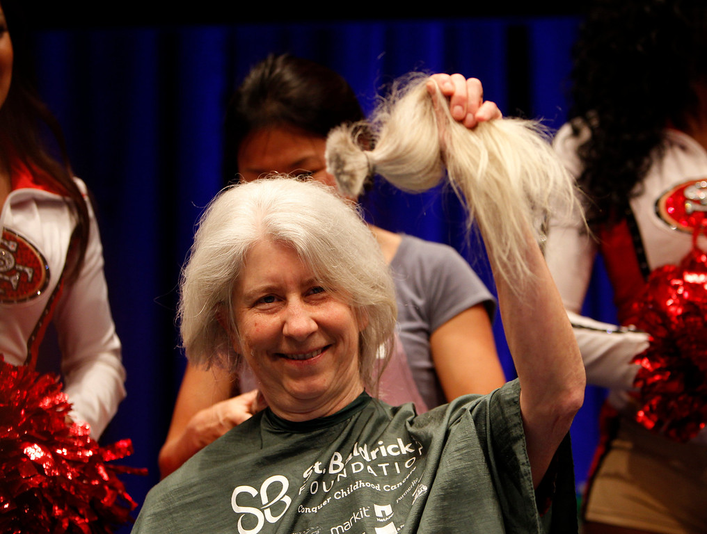. Pia Chamberlain holds a ponytail from her hair before she had her head shaved for the St. Baldrick\'s Day head shaving event in support of research for pediatric cancer sponsored by the St. Baldrick\'s Foundation in the NetApp gymnasium at NetApp in Sunnyvale, Calif., on Thursday, March 14, 2013.  (Nhat V. Meyer/Staff)