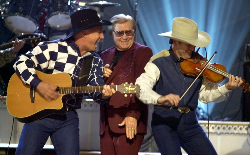 ". FILE - In this Nov. 7, 2001 file photo, Garth Brooks, left, and George Jones, center, perform their duet ""Beer Run\"" at the Country Music Association Awards show in Nashville, Tenn.   The fiddle player at right is unidentified.   Jones, the peerless, hard-living country singer who recorded dozens of hits about good times and regrets and peaked with the heartbreaking classic \""He Stopped Loving Her Today,\"" has died. He was 81. Jones died Friday, April 26, 2013 at Vanderbilt University Medical Center in Nashville after being hospitalized with fever and irregular blood pressure, according to his publicist Kirt Webster.(AP Photo/M. Spencer Green, file)"