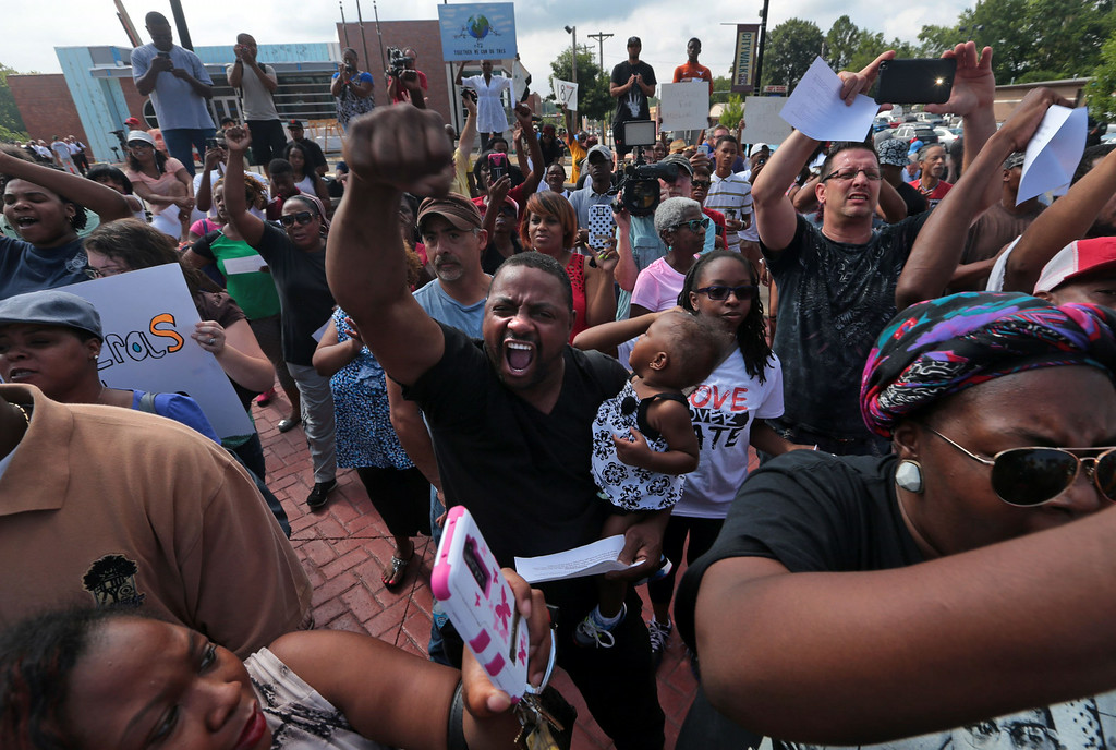 ". ""He was my second cousin. It\'s just so wrong,\"" said Tony Petty who holds his granddaughter as joins a protest against the police shooting of Michael Brown in front of the Ferguson police station on Monday, Aug. 11, 2014. Marchers are entering a third day of protests. (AP Photo/St. Louis Post-Dispatch, Laurie Skrivan)"