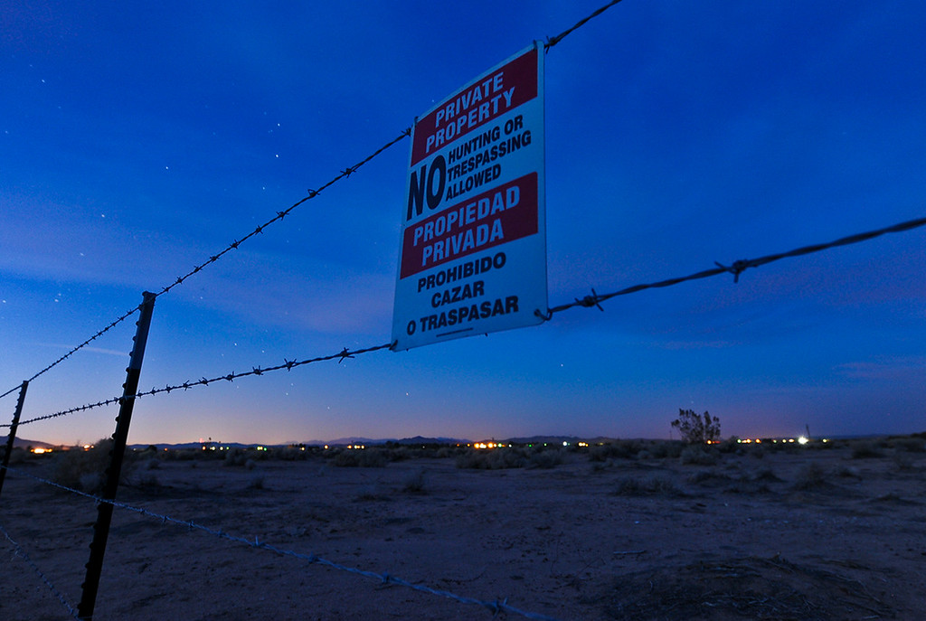 """. Barbed wire and a \""""no trespassing\"""" sign is posted in a parcel of land in Hinkley, Calif. on Monday, March 25, 2013. In the last two years, residents have become aware that a toxic water plume continues to grow below their small town, and the fate of Hinkley\'s future remains grim. (Rachel Luna / San Bernardino Sun)"""