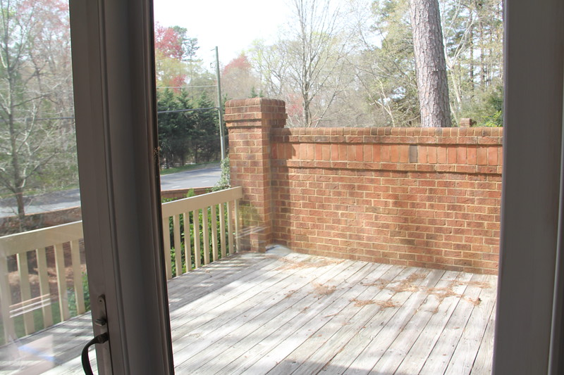 """looking through the glass doors in the main room onto the """"deck"""" which we have permission to turn into a screened porch"""