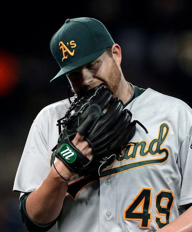. Oakland Athletics pitcher Brett Anderson bites his glove after pitching against the Detroit Tigers in the seventh inning of a baseball game in Detroit, Wednesday, Aug. 28, 2013. (AP Photo/Paul Sancya)