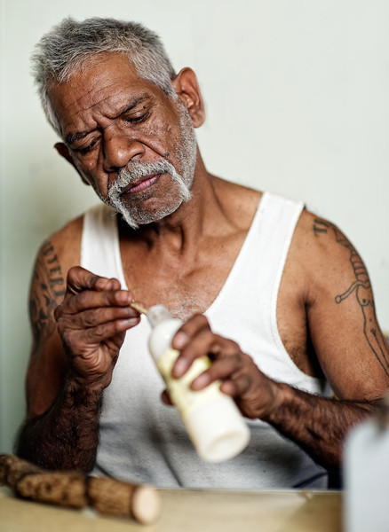 Aboriginal Artist using a brush to complete a message stick