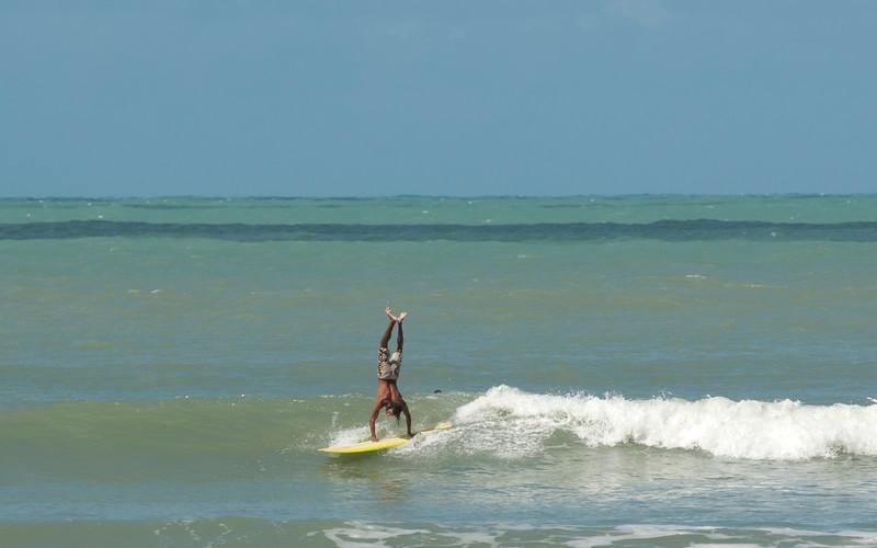 A man doing a hand stand on a longboard, Praia do Pipa, Rio Grande du Norte, Brazil.