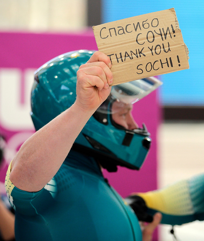 . One of the Australian team AUS-1 members holds a thank you note after their third run during the men\'s four-man bobsled competition final at the 2014 Winter Olympics, Sunday, Feb. 23, 2014, in Krasnaya Polyana, Russia. (AP Photo/Jae C. Hong)