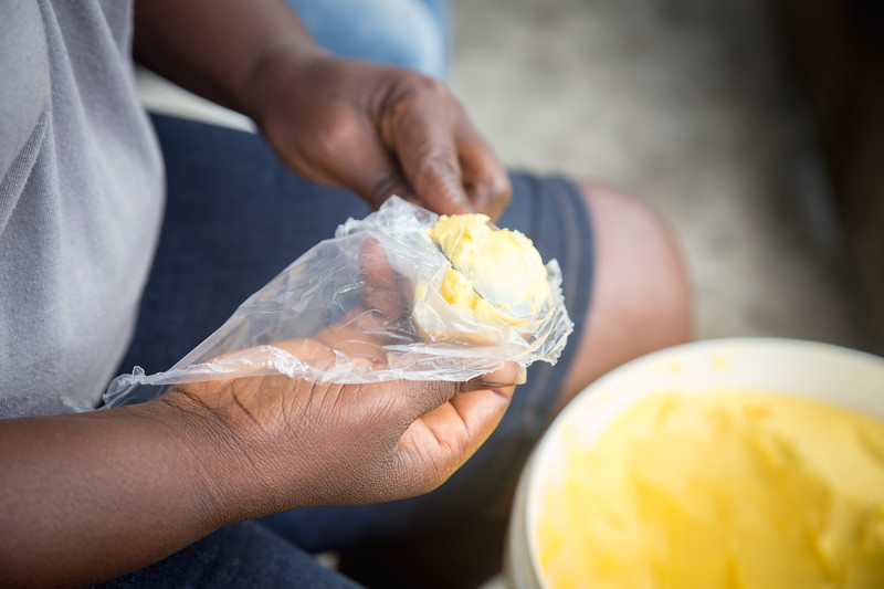 Monrovia, Liberia October 6, 2017 - Jacqueline Clinton,  a student in the REVSLA program who owns her own general store, makes packets of butter to sell.