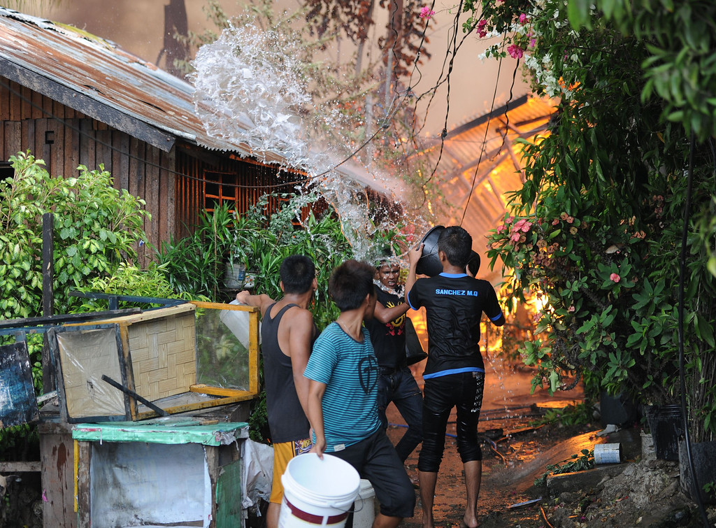 . Residents using pails douse their burning houses with water during a fire fight between government forces and Muslim rebels as stand-off entered its fourth day in Zamboanga City on the southern island of Mindanao on September 12, 2013.   AFP PHOTO/TED ALJIBE/AFP/Getty Images