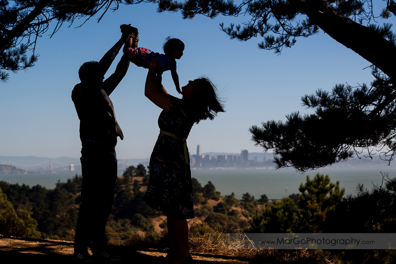 silhouette of parents holding up little boy with view of San Francisco at Richmond Keller Beach