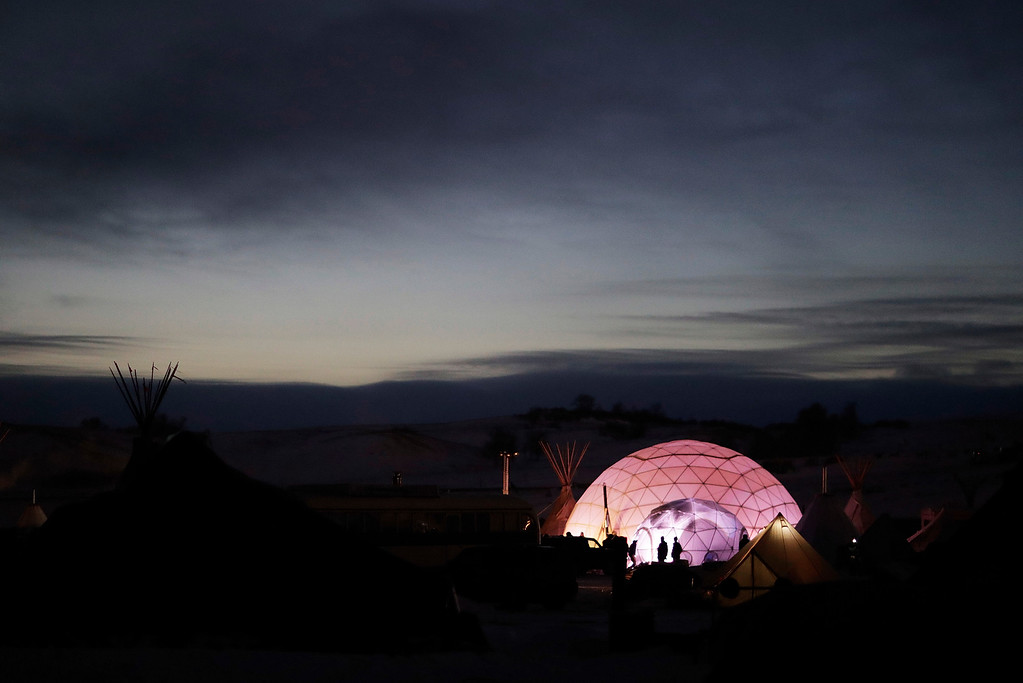 . People stand outside a dome used as a community center and sleeping area at the Oceti Sakowin camp where people have gathered to protest the Dakota Access oil pipeline in Cannon Ball, N.D., Friday, Dec. 2, 2016. (AP Photo/David Goldman)