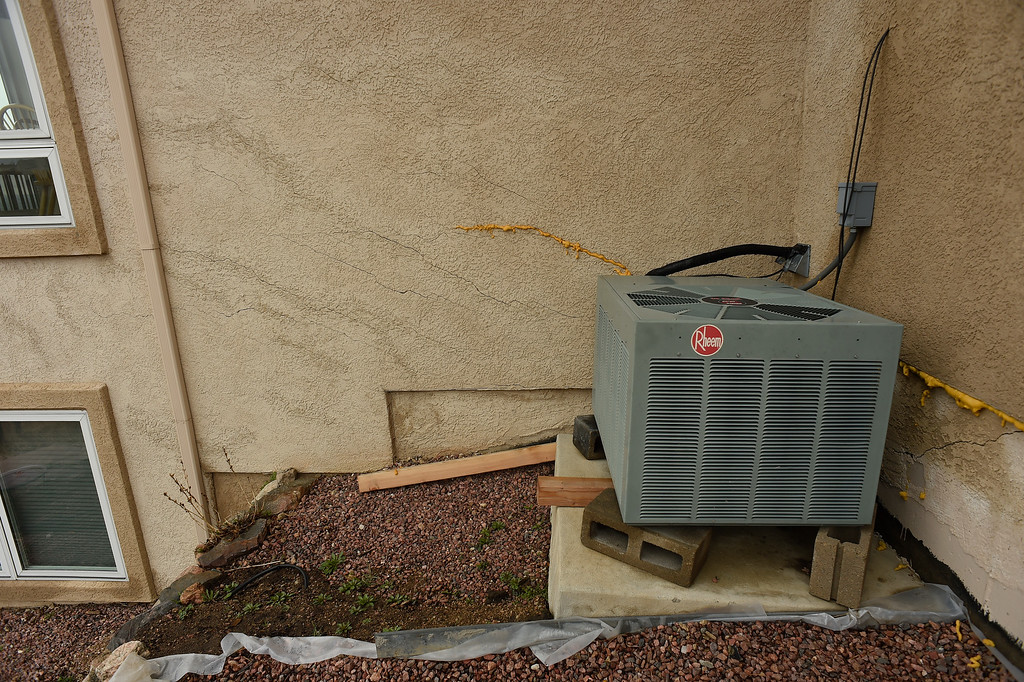 . The air conditioning unit of Homeowner Denny  Cripps sits on concrete blocks because the house is slowly sinking below it in Broadmoor Bluffs on April 11, 2016 in Colorado Springs, Colorado.  The Cripps are among 200 homeowners who have applied for federal bailouts because their home is being eaten up by collapsing expansive soil that is part of an ancient and massive landslide area.  Their home has cracked walls, uneven floors and is literally sliding down the mountain.  It is a problem that city officials have known about since the mid-1990\'s when city planners approved developments on what geologists have called some of the most unstable geology on the front range.  (Photo by Helen H. Richardson/The Denver Post)