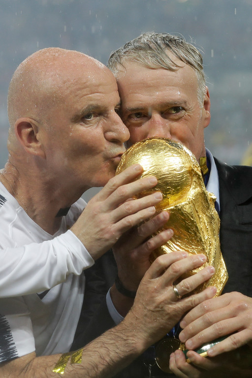 . France head coach Didier Deschamps, right, kisses the trophy at the end of the final match between France and Croatia at the 2018 soccer World Cup in the Luzhniki Stadium in Moscow, Russia, Sunday, July 15, 2018. (AP Photo/Matthias Schrader)