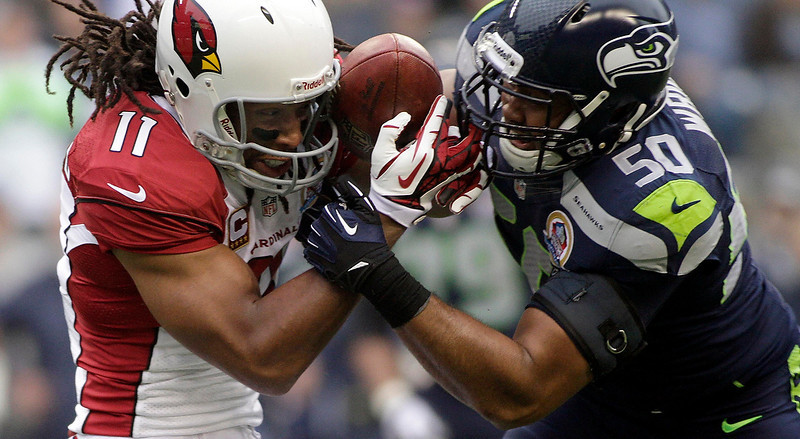 . Arizona Cardinals wide receiver Larry Fitzgerald (11) battle for the football with Seattle Seahawks K.J. Wright (50) on a pass during the first quarter of their NFL football game in Seattle, Washington, December 9, 2012. The Seahawks Bobby Wagner would intercept the football on the play. REUTERS/Robert Sorbo