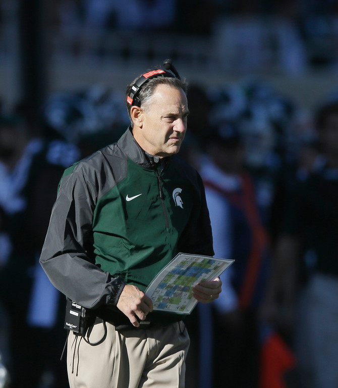 . Michigan State head coach Mark Dantonio walks the sidelines during the first half of an NCAA college football game against Michigan in East Lansing, Mich., Saturday, Oct. 25, 2014. (AP Photo/Carlos Osorio)