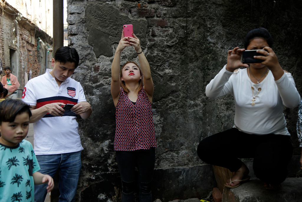 . Ethnic Chinese people take pictures of a procession of lion dancers on the first day of Lunar New Year in Kolkata, India, Friday, Feb. 16, 2018. People in Asia and around the world are celebrating the Lunar New Year on Friday with festivals, parades and temple visits to ask for blessings. This year marks the year of the dog, one of the 12 animals in the Chinese astrological chart. (AP Photo/Bikas Das)