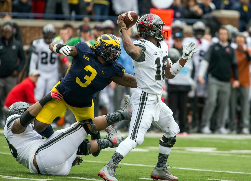 . Michigan defensive lineman Rashan Gary (3) tries to sack Ohio State quarterback J.T. Barrett (16) in the first quarter of an NCAA college football game in Ann Arbor, Mich., Saturday, Nov. 25, 2017. (AP Photo/Tony Ding)