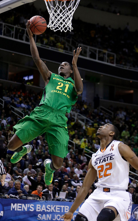 . Oregon guard Damyean Dotson (21) shoots over Oklahoma State guard Markel Brown (22) during the first half of a second-round game in the NCAA college basketball tournament in San Jose, Calif., Thursday, March 21, 2013. (AP Photo/Ben Margot)