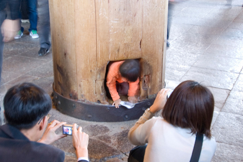 Boy crawling out of a hole in Pillar in Todaiji Temple - Nara, Japan