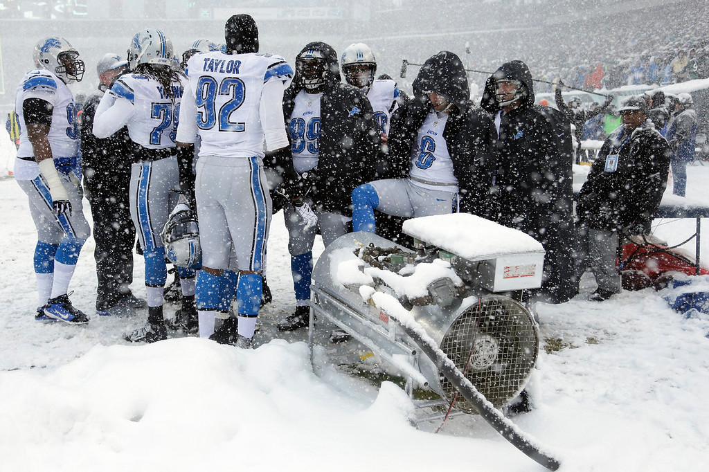. Detroit Lions players warm themselves during the first half of an NFL football game against the Philadelphia Eagles, Sunday, Dec. 8, 2013, in Philadelphia. (AP Photo/Matt Rourke)