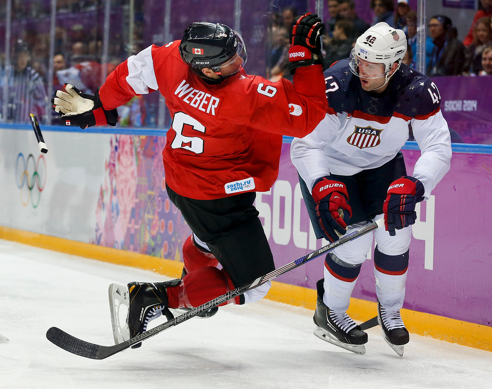 . Canada defenseman Shea Weber, left, trips over USA forward David Backes during the third period of a men\'s semifinal ice hockey game at the 2014 Winter Olympics, Friday, Feb. 21, 2014, in Sochi, Russia. (AP Photo/Julio Cortez)