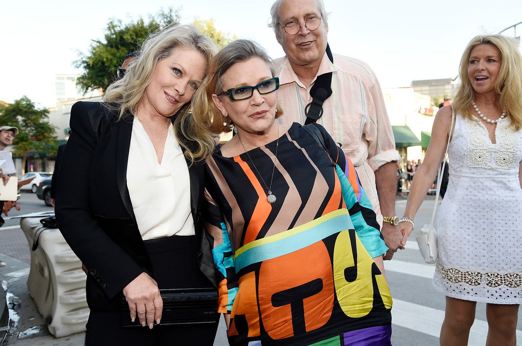 """. Beverly D\'Angelo, left, a cast member in \""""Vacation,\"""" is joined by Carrie Fisher as fellow cast member Chevy Chase and his wife Jayni look on at the premiere of the film on Monday, July 27, 2015, in Los Angeles. (Photo by Chris Pizzello/Invision/AP)"""