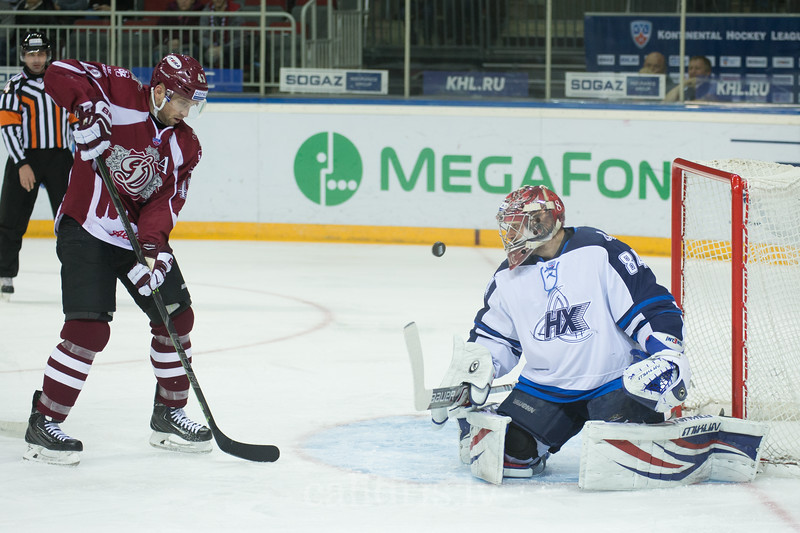 Tim Sestito (43) of Dinamo Riga plays in front of the goalkeeper of Neftekhimik Nizhnekamsk Ivan Lisutin (84)