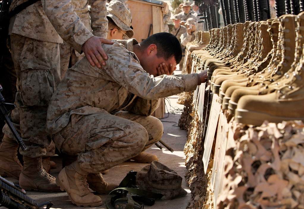 . In this Feb. 2, 2005 file photo made by Associated Press photographer Anja Niedringhaus, a U.S. Marine cries during the memorial service for 31 killed U.S. servicemen at Camp Korean Village, near Rutbah, western Iraq.  (AP Photo/Anja Niedringhaus, File)