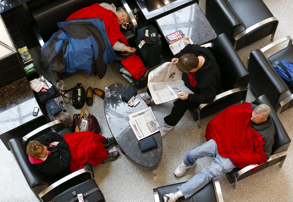 . Stranded travelers rest in the main terminal at Hartsfield-Jackson Atlanta International Airport during a severe winter storm in Atlanta, Georgia, USA, 12 February 2014. More than 1,800 flights have been cancelled at the airport. Ice and snow in the metro Atlanta area is expected to make travel treacherous and cut electricity to thousands of customers.  EPA/ERIK S. LESSER