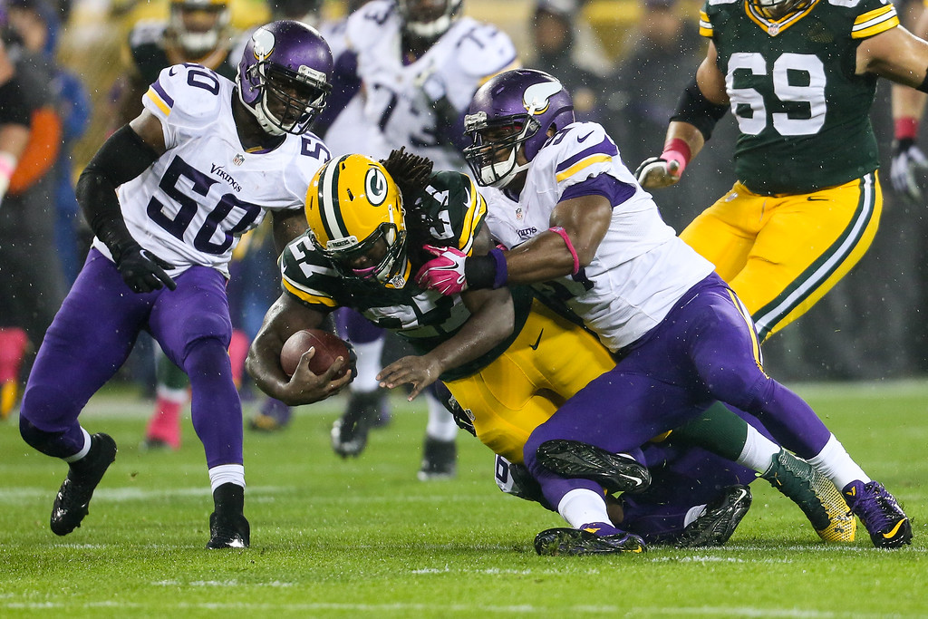 . GREEN BAY, WI - OCTOBER 2: Eddie Lacy #27 of the Green Bay Packers is tackled by Gerald Hodges #50, Robert Blanton #36 and Everson Griffen #97 of the Minnesota Vikings on October 02, 2014 at Lambeau Field in Green Bay, Wisconsin. (Photo by John Konstantaras/Getty Images)