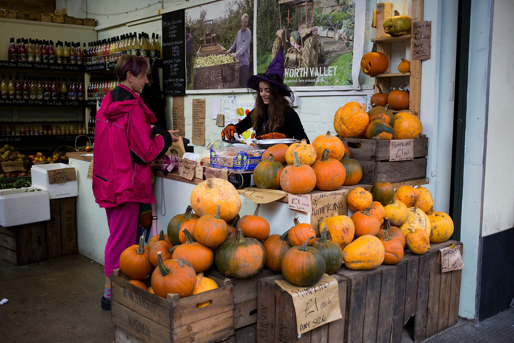 . A worker wearing a witches hat serves a customer as pumpkins are displayed on sale at the Chegworth Valley farm stall at Borough Market in south London, Thursday, Oct. 31, 2013.  Pumpkins are traditionally bought and decorative faces carved out of them by people to mark Halloween which occurs annually around the world on October 31.  (AP Photo/Matt Dunham)
