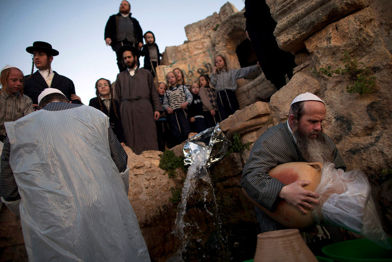 . Ultra-Orthodox Jews collect water to make matza during the Maim Shelanoo ceremony at a mountain spring, in Jerusalem, Sunday, March 24, 2013. The water is used to prepare the traditional unleavened bread for the high holiday of Passover which begins Monday. (AP Photo/Oded Balilty)
