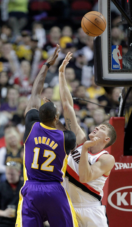 . Los Angeles Lakers center Dwight Howard, left, shoots over Portland Trail Blazers center Meyers Leonard during the second half of an NBA basketball game in Portland, Ore., Wednesday, April 10, 2013.  Howard scored 20 points and pulled in 10 rebounds as the Lakers won 113-106.(AP Photo/Don Ryan)