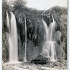 """Title: """"Spearfish Falls."""" Black Hills, Dak.<br /> Man standing below two waterfalls. 1889.<br /> Repository: Library of Congress Prints and Photographs Division Washington, D.C. 20540"""