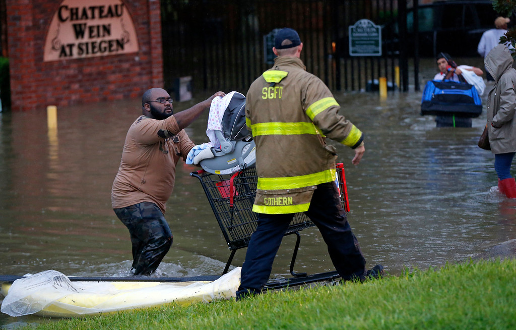 . A member of the St. George Fire Department assists residents as they wade through floodwaters from heavy rains in the Chateau Wein Apartments in Baton Rouge, La., Friday, Aug. 12, 2016. Heavy downpours pounded parts of the central U.S. Gulf Coast on Friday, forcing the rescue of dozens of people stranded in homes by waist-high water. (AP Photo/Gerald Herbert)