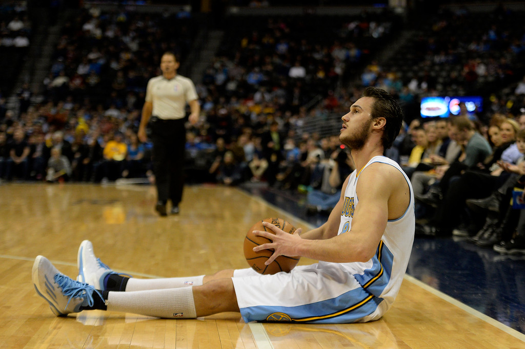 . DENVER, CO - MARCH 03: Danilo Gallinari (8) of the Denver Nuggets sits on the floor after colliding with and being called for charging Ersan Ilyasova (7) of the Milwaukee Bucks during the first quarter of action. The Denver Nuggets hosted the Milwaukee Bucks at the Pepsi Center on Tuesday, March 3, 2015. (Photo by AAron Ontiveroz/The Denver Post)