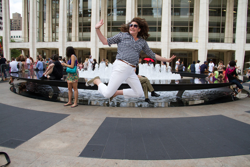 Valerie jumps in front of fountain. She's my jumping buddy.