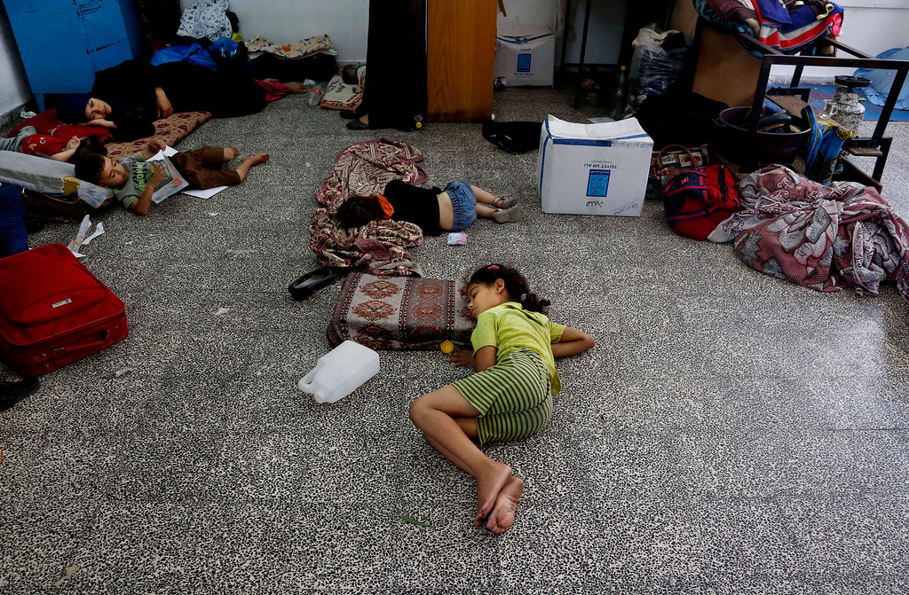 . Palestinian children lay on the floor at the Abu Hussein U.N. school, hit by an Israeli strike earlier, in the Jebaliya refugee camp, northern Gaza Strip, Wednesday, July 30, 2014. Israeli tank shells slammed into a crowded U.N. school sheltering Gazans displaced by fighting on Wednesday, killing more than a dozen and wounding tens after tearing through the walls of two classrooms, a spokesman for a U.N. aid agency and a health official said. The Israeli military said mortar shells had been fired from near the school, and that soldiers fired back. (AP Photo/Hatem Moussa)